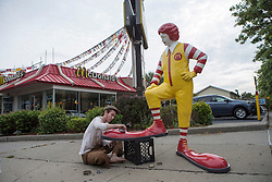 "Banksy graffiti art in New York City. Wednesday, 16 October 2013. Banksy's piece for the 16th day of his artist's residence in New York City; a boy polishes the shoes of a statue of Ronald McDonald, McDonald's Restaurant mascot. The piece is located in the South Bronx. Banksy is doing a month long artist in residence on the streets of New York called ""Better Out Than In."" Picture by Michael Graae / i-Images"
