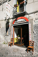 "NAPLES, ITALY - 10 OCTOBER 2018: The entrance of La Taverna a Santa Chiara, a tavern in the historical center of Naples, Italy, on October 10th 2018.<br /> <br /> The idea of the founders Nives Monda and Potito Izzo (two really unusual names in southern Italy) was to create a ""taste gate"" of Campania products. La Taverna a Santa Chiara, founded in 2013, is a modern tavern whose strengths are the choice of regional and seasonal products and mostly small producers. Small restaurant, small producers.<br /> The two partners tried to put producers and consumers in direct contact, skipping the distribution, and managing to reduce the costs of the products considerably. Nives and Potito managed to create a simple kitchen, at moderate costs but with high quality raw materials.<br /> ""A different restaurant idea,"" says Nives, ""the producers deliver their products at low prices and the tavern manages to make traditional dishes with niche products"".<br /> Nives Monda has been a labor consultant for 20 years. Potito Izzo is the chef who has always been loyal to the  family cuisine. When he embraced the idea of Nives he found in the tavern the natural place to express the tradition of Neapolitan cuisine. Nives defines him as a ""comfort food chef"". Their partnership is a true friendship that has lasted for over 10 years."