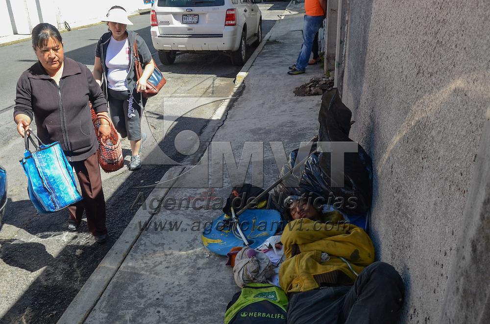 Toluca, México.- Durante la mañana y rodeado de sus pertenencias, un hombre toma un siesta en la banqueta de la calle constituyentes frente al estadio Nemesio Diez. Agencia MVT / Arturo Hernández.