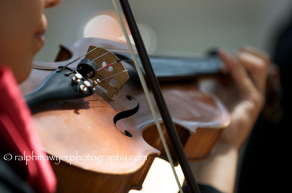 Close-up of violin fine tuners, with bow, bridge,  and strings, being played by female mararchi.