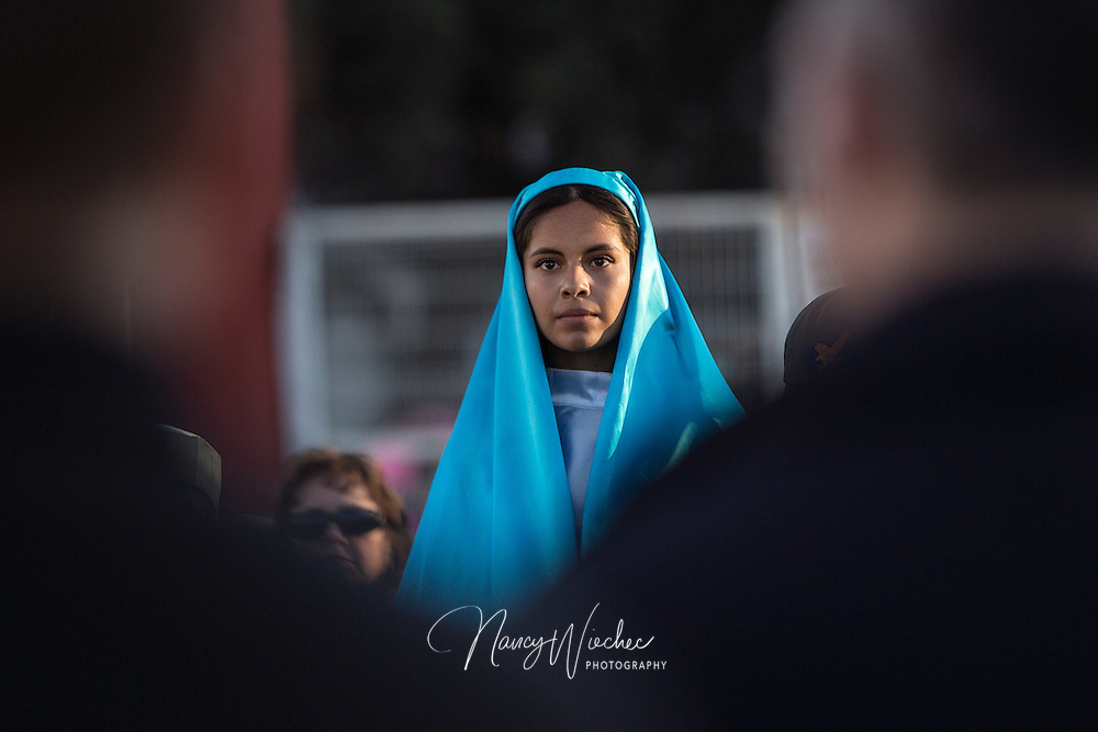"""Kenia Salas, playing the part of Mary, looks out into a crowd during a bi-national """"posada"""" Dec. 20 in Nogales, Sonora. The commemoration of Mary and Joseph's search for shelter before the birth of Christ was held by the Kino Border Initiative and Dioceses Without Borders to reflect on the struggles of migrants and migrant families. (CNS photo/Nancy Wiechec)"""