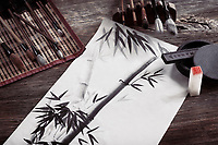 Japanese sumi-e painting of a bamboo on rice paper and artist tools, brushes, ink stone and seal, artistic table top still life on rustic wood background.