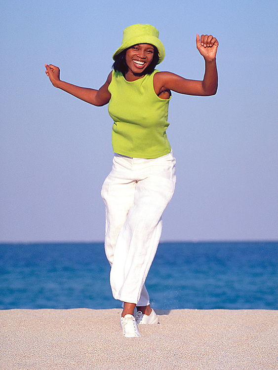 Smiling young black woman dancing on beach