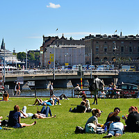 People Sunning in King's Garden in Stockholm, Sweden <br /> While I was traveling in Scandinavia in the spring, it was cold, wet and raining for nearly three weeks. But on the first day I visited Stockholm, the sky was blue and the temperature soared. The locals relished the occasion by rolling up their sleeves and pants legs and basking in the sunshine at Charles XII Square in the King's Garden.