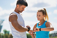 Young attractive couple looking at their watch in park