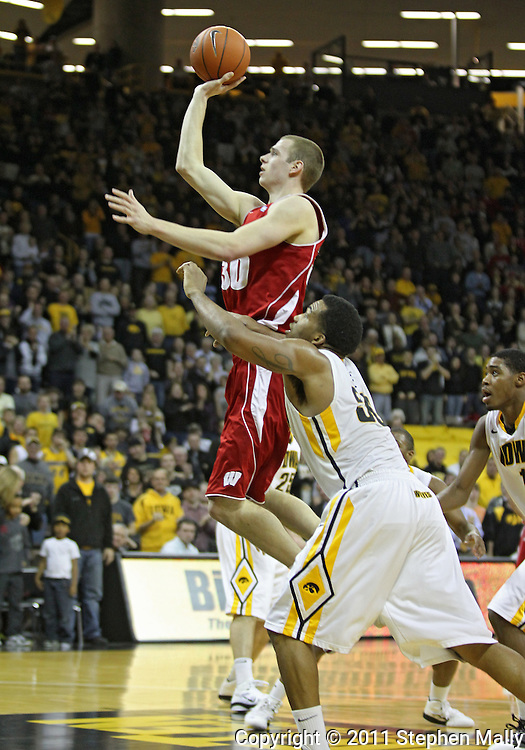 February 09 2011: Wisconsin Badgers forward Jon Leuer (30) puts up a shot over Iowa Hawkeyes forward Jarryd Cole (50) during the first half of an NCAA college basketball game at Carver-Hawkeye Arena in Iowa City, Iowa on February 9, 2011. Wisconsin defeated Iowa 62-59.