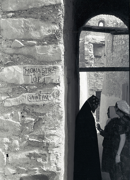 At St. Paul's Monastery, ancient (5th century) Coptic structure still in use, two women consult a priest.  They are in the shadow of an arched passageway.  The priest's head is bent to listen, while one of the women gestures towards him.