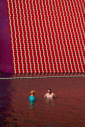 Swimmers at the Serpentine's lido are dwarfed by artist Christo's 20m high installation on The Serpentine made from over 7000 barrels, titled The Mastaba, which will be on the Serpentine until 23 September 2018. The Installation is comprised of 7,506 horizontally stacked barrels. It is 20m high, 30m wide and 40m long. Hyde Park, London, June 18 2018.