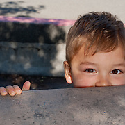 the upper part of a young boy's face, with eyes full of fun and happiness, peeks from behind a concrete table, his right hand gripping the edge
