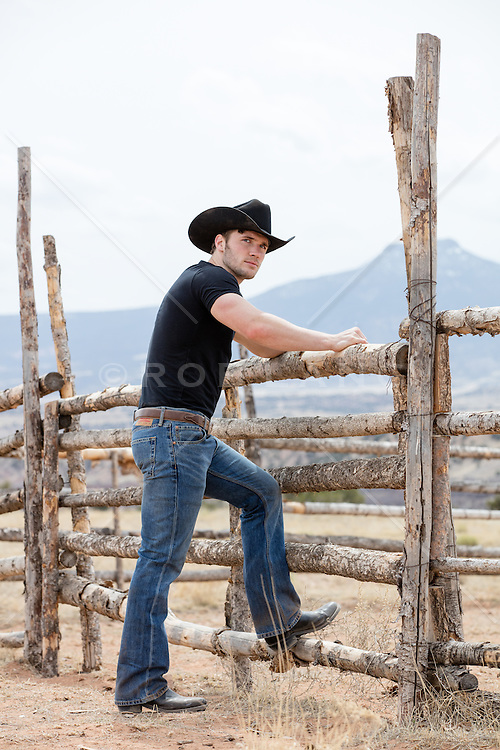 rugged cowboy leaning on a rustic fence in the mountains