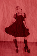 Digitally enhanced colourful image of a female model wearing lolita style dress with high heeled boots
