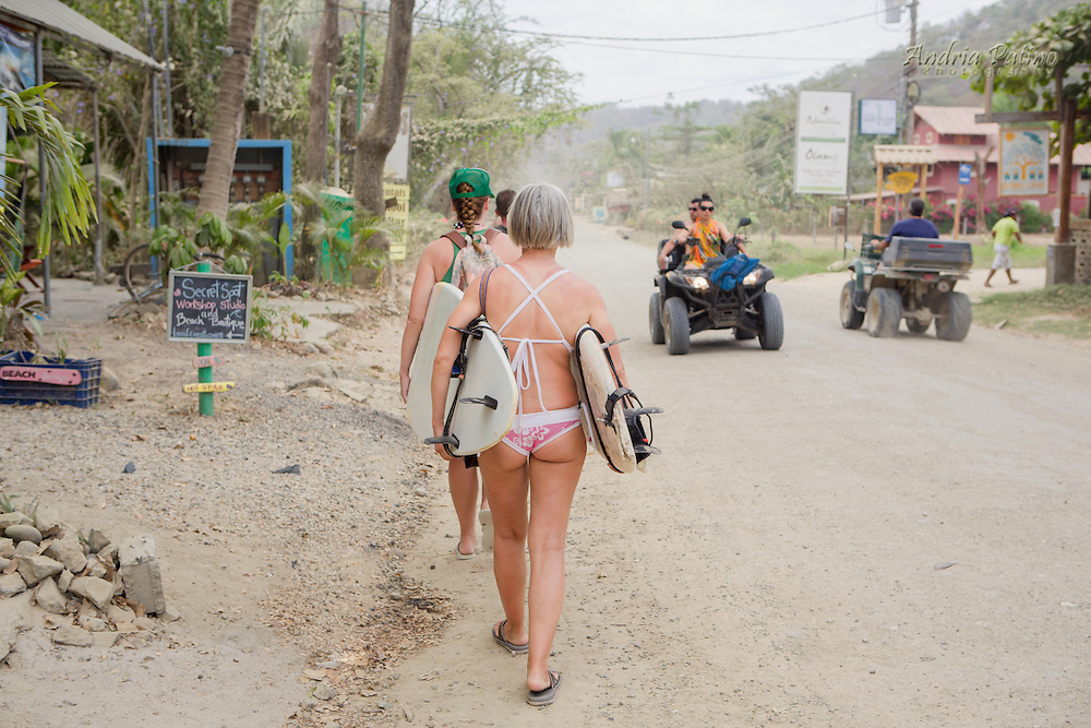 Women carrying surfboards along side road, Santa Teresa, Costa Rica