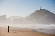 Woman walking on Zurriola beach in San Sebastian (Spain)