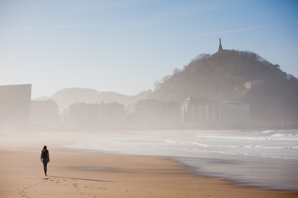 Woman walking on Zurriola beach in San Sebastian (Spain)