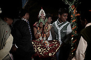 Mera is not allowed to walk to the Wedding Grounds and is carried by two men, while she is covering her face with green leaves. Varanasi, India.