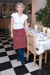 Owner of Polish Restaurant standing by set tables,