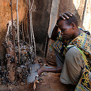 Benin, Natitingou November 29, 2006 - A guinea-hen is sacrificed as part of a Voodoo temple ceremony before a Scarification ceremony. It is used as a form of initiation into adulthood, beauty and a sign of a village, tribe, and clan.