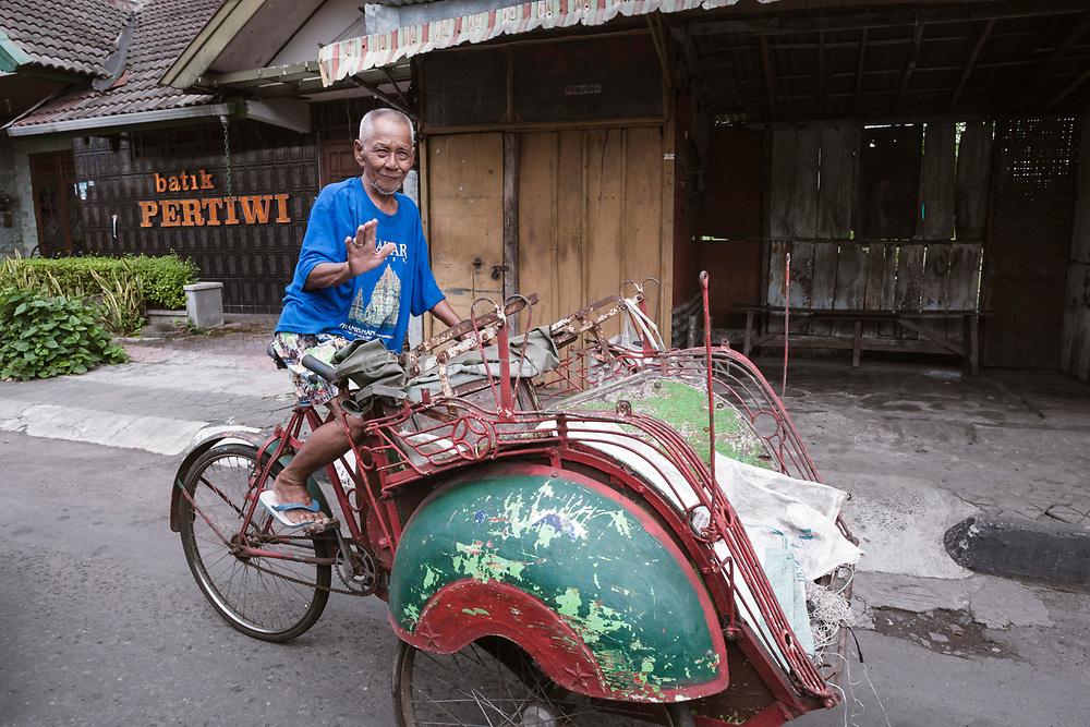A bekak rider waves as he rides past through the streets of Yogyakarta.