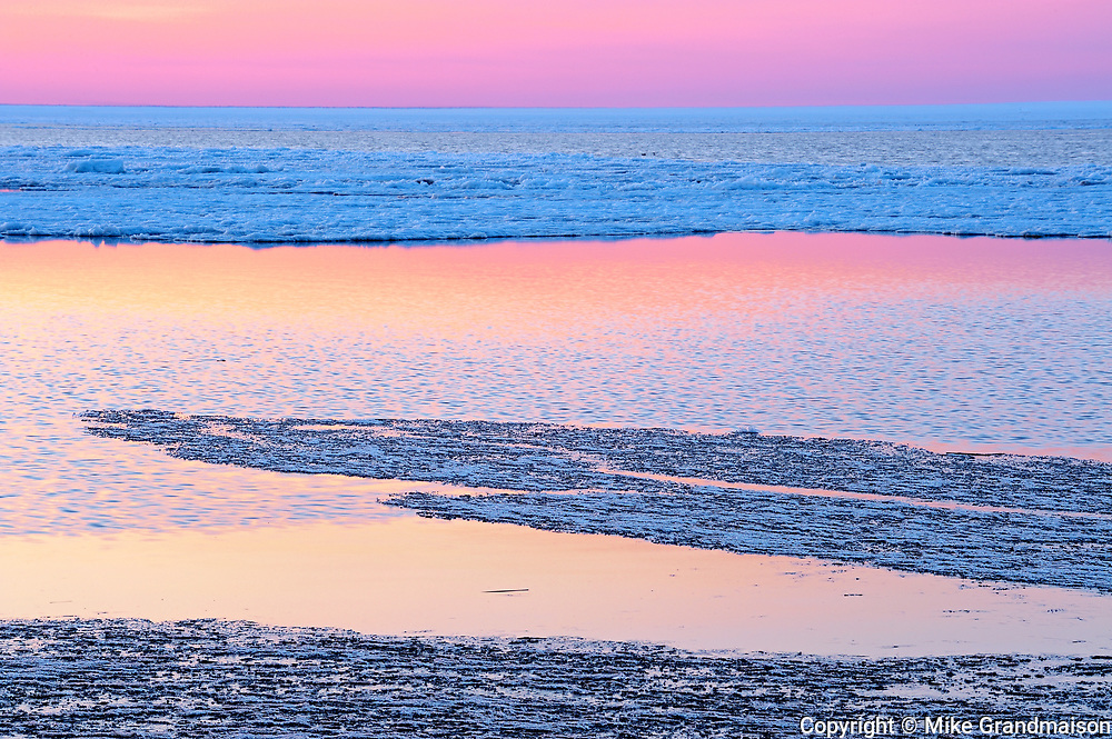 Lake Manitoba at dusk partially covered in spring ice
