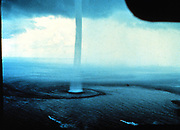 A waterspout, a type of tornado that occurs over water. Waterspouts are spinning columns of rising moist air that typically form over warm water. Waterspouts can be as dangerous as tornadoes and can feature wind speeds over 200 kilometers per hour. Many waterspouts form away from thunderstorms and even during relatively fair weather. Waterspouts may be relatively transparent and initially visible only by the unusual pattern they create on the water. The above image was taken in 1969 from an aircraft off the Florida Keys,