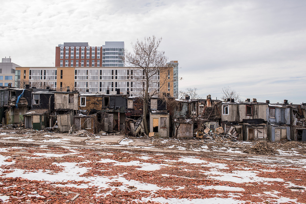 Baltimore, Maryland - March 07, 2014: Rowhomes slated to be razed sit across the street from the new Henderson-Hopkins community school. Blocks of rowhomes are being torn down to make way as part of the controversial East Baltimore Development Area project. Parts of the Johns Hopkins East Baltimore campus loom large over the neighborhood.<br /> <br /> Henderson-Hopkins is a K-8 community school in East Baltimore. The school's library, gymnasium, auditorium, Early Childhood Center, and family resource center are open to the surrounding community. The school is funded through a partnership with Baltimore City, Johns Hopkins and the Harry and Jeanette Weinberg Foundation.