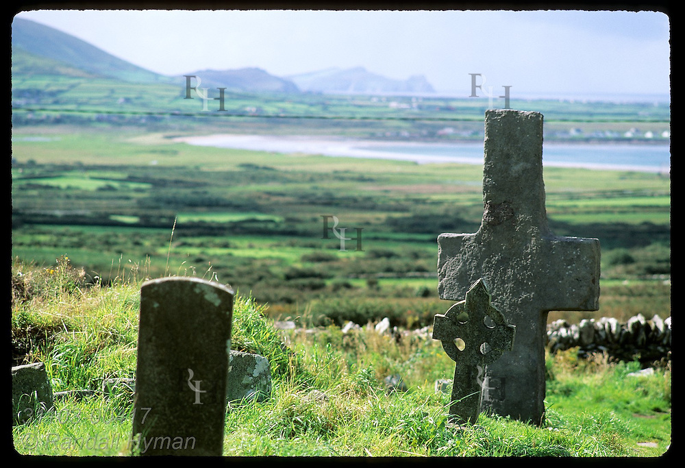 Stone cross (7th-8th c.) and Celtic cross in cemetery at Kilmalkedar Church overlook Dingle Peninsula pastures and shore; Ireland.
