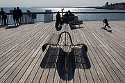 The figures of visitors including a scooting girl with the shadows of a bench on Hastings Pier, on 29th April 2017, at Hastings, East Sussex, England.