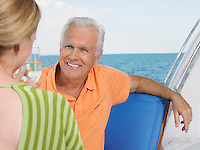 Middle-aged couple drinking wine on yacht