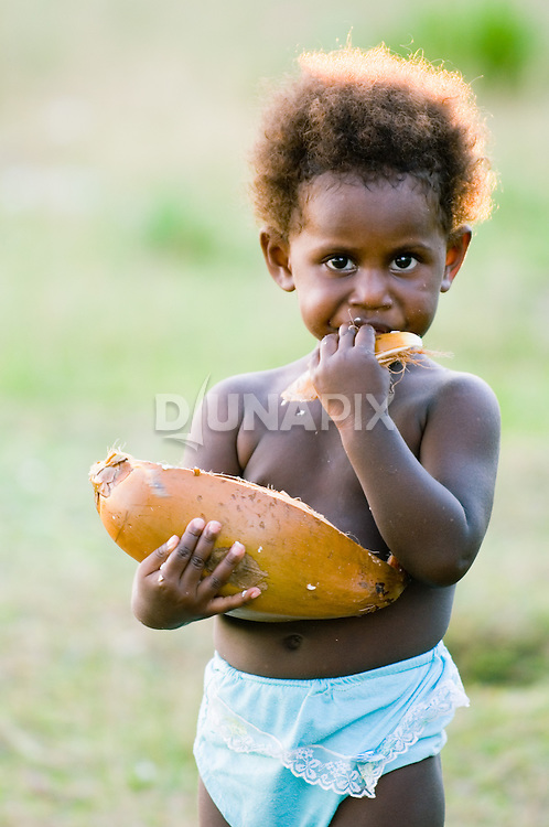A girl gnaws on coconut in Waghena village.