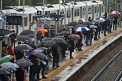 ©Licensed to London News Pictures 14/10/2019.<br /> Pettswood,UK. Umbrellas up on the platform. A wet weather morning for these London commuters at Pettswood railway station in Pettswood, South East London. Forecasters say more than two inches of rain could fall within 12 hrs today. Photo credit: Grant Falvey/LNP