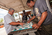 Bahamian men play checkers at a roadside food stall at Potter's Cay in Nassau, Bahamas.