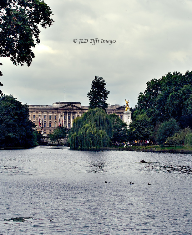Buckingham Palace and Queen Victoria monument seen beyond the lake, St. James's Park, London.  The Queen's flag is not present, indicating that she is not in residence.  The expanse of lake with overhanging trees makes the scene look more romantically rural than it really is.