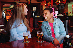 Care manager and young woman with Cerebral Palsy sitting together in pub drinking beer and laughing,