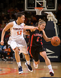 Georgia guard Ashley Houts (1) shields Virginia guard Britnee Millner (12) from the ball with an elbow.  The #15 ranked Virginia Cavaliers defeated the Georgia Lady Bulldogs 62-60 in NCAA Women's Basketball at the John Paul Jones Arena on the Grounds of the University of Virginia in Charlottesville, VA on January 2, 2009.