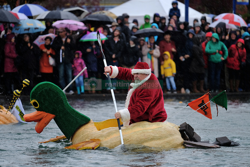 A man dressed as Sant paddles a giant pumpkin duck across Lake of the Commons at the 14th annual West Coast Giant Pumpkin Regatta in Tualatin, Ore. on October 21, 2017. (Photo by Alex Milan Tracy)