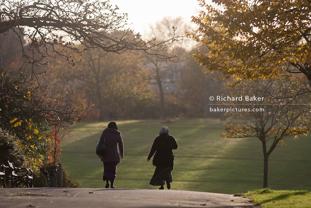 Two Muslim women walk through Brockwell Park in Herne Hill, Lambeth SE24 south London.