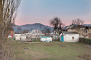 A caravan trailer marks the boundary between a field and some collapsed buildings. The mountains in the background and the pink of the sunset are an unsettling image before all this mess.