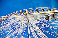 Chartres, France. Looking up to the top of the Ferris wheel at the colored gondolas and deep blue sky.