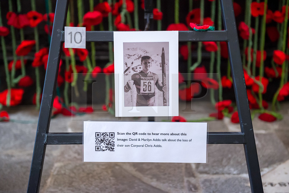 """© Licensed to London News Pictures. 27/10/2018. Bristol, UK. The Royal British Legion launch this year's Poppy Appeal, """"One thousand poppies, for one hundred years, for one million lives"""" at Bristol Cathedral. Picture inside Bristol Cathedral of a commemoration for Corporal Chris Addis who was killed in Bosnia in 1998. For the launch of the 2018 Bristol Poppy Appeal at 11am on 27 October, The Royal British Legion recreated a scene from the end of WW1 outside Bristol Cathedral on College Green, and Colonel Clive Fletcher-Wood read the war poem In Flanders Fields. They were joined by a Bugler and the Bristol Military Wives Choir who performed songs from their new album 'Remember'. Staff at MOD Filton filled 400 sandbags with eight tonnes of sand to build trenches and recreate 'Flanders Fields' and planted over 1000 waterproof poppies on College Green. Poppies and sandbags can be sponsored by individuals wanting to remember those who fought and died in conflict. There were re-enactors in WW1 uniform from Somerset Light Infantry (known as the West Country Tommys), as well as medics and nurses with equipment from the time. Bristol's own 'War Horse' (Buzz from Blagdon Horsedrawn Carriages) was on College Green behind the improvised barbed wire to represent the 350,000 horses that left Avonmouth for the frontline during WW1. There are also 10,000 knitted poppies on display both in and outside Bristol Cathedral following 'The Charfield Yarn Bombers' incitement to locals to get knitting to mark the occasion, with a display inside the Cathedral organised by Helen Date. Photo credit: Simon Chapman/LNP"""