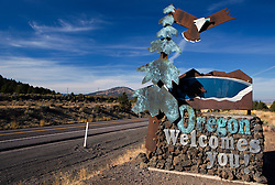 """Oregon sculpture welcome sign with a bald eagle soaring over an evergreen tree and mountain with text """"Oregon Welcomes You"""", US 97 Oregon state line."""