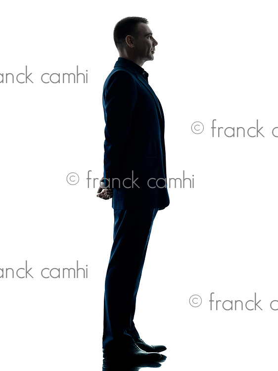one caucasian business man standing profile silhouette isolated on white background