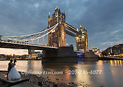 Image of a bride and groom embracing in front of Tower Bridge in London, England.