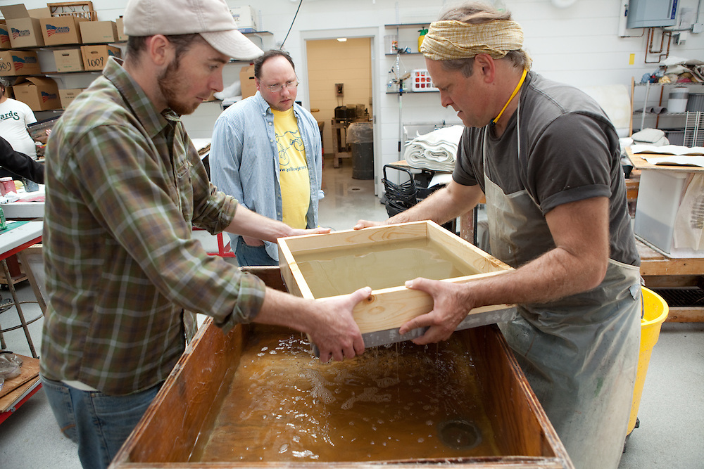After the pulp is evenly distributed in the mould, it is lifted to drain the water. Drew Cameron (left), Matthew Reedy (middle) and Robert Possehl (right) forming a sheet of paper .Combat Paper participants in a workshop in the Paper Lab in the Department of Art at the University of Wisconsin-Madison.