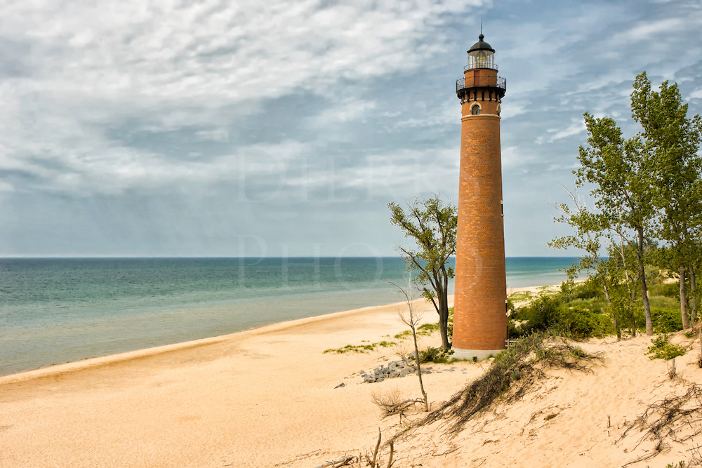 Although this image looks like something right out of the Caribbean, Little Sable lighthouse is about halfway up the eastern side of Lake Michigan from Chicago. Certainly one of the most scenic lighthouses in the country, the original brick finish was restored when the modern steel plating was removed after decommissioning by the Coast Guard.<br /> <br /> I was very surprised to see how much sand there is in this playground area of Michigan near Sleeping Bear Dunes. Here the high dunes come down to a wide flat beach. This long view out over the lake goes for miles, and rain falling can be faintly seen off in the distance.