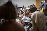 RIO DE JANEIRO, BRAZIL - JANUARY 24: &quot;Av&ocirc; do Santo,&quot; or spiritual grandfather, Luis de Omolu, at right, blesses newly initiated practitioners during a candomble ceremony, in Rio de Janeiro, Brazil, on Saturday, Jan. 23, 2015. Brazil's Afro-Brazilian religions which in recent years have come under increasing threats and prejudice, particularly from the growing number of evangelical churches. Candombl&eacute; originated in Salvador, Bahia at the beginning of the 19th century when enslaved Africans brought their beliefs with them. Umbanda and candombl&eacute; are Afro-Brazilian religions practiced in mostly Brazil. <br /> (Lianne Milton for the Washington Post)