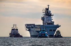 © Licensed to London News Pictures. 07/12/2016. Portsmouth, UK. Tugs tow the former Royal Navy aircraft carrier HMS Illustrious from Portsmouth through The Solent  on her final voyage to a scrap yard. Illustrious, the last of the Invincible Class carriers, has been sold to the Leyal Ship Recycling and Dismantling company in Aliaga, Turkey - the same yard dismantled her sister ships Ark Royal and Invincible. Photo credit: Peter Macdiarmid/LNP