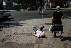 A local woman stands near a dead man after a mortar attack by the Ukrainian army of the center of Donetsk, Ukraine, 14 August 2014. Reports state that ten local people where wounded and one killed after the mortar attack.