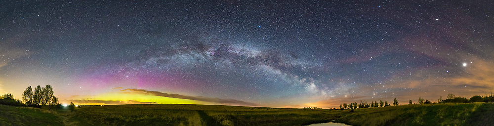 The arch of the northern summer Milky Way across the Alberta prairie sky on a spring night, with the glow of aurora to the north at left. At right are Saturn and Antares in Scorpius low in the south, and bright Jupiter at far right, with Spica to the left of Jupiter and Arcturus above at top right. The Summer Triangle stars are at centre straddling the Milky Way.<br /> <br /> Shot from home with the Rokinon 14mm SP lens at f/2.5 and Canon 6D at ISO 6400 for a stitch of 9 exposures, each 30 seconds. Stitched with PTGui. This was about 1 am May 16, just before local moonrise.