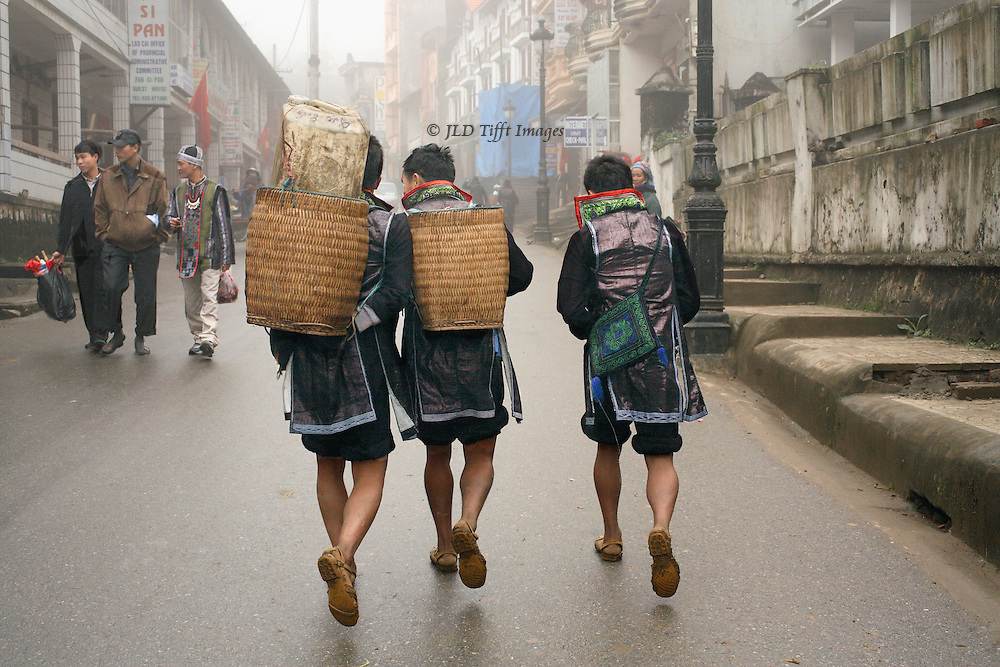 """Three """"black Hmong"""" men walking uphill on a street in the town of SaPa, North Vietnam.  They wear traditional indigo-dyed garb and carry baskets on their backs, seen from the back, their powerful legs indicate a life of climbing hills.  Three  others in more contemporary dress, carrying shopping bags, approach toward us."""