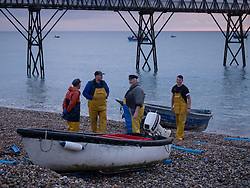 © Licensed to London News Pictures. 26/10/2016. Selsey, UK. Fishermen heading out at dawn next to Selsey Lifeboat Station this morning, 26th October 2016. The current station, re-built in 1958, currently houses the 'Betty and Thomas Moore' D-Class lifeboat. The station has a history of over 150 years of active lifeboat service. Photo credit: Rob Arnold/LNP